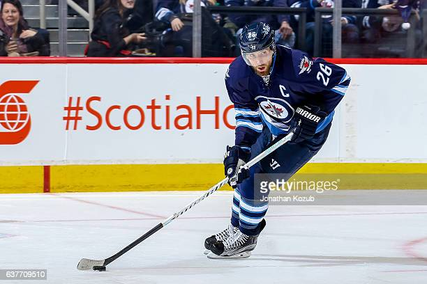 Blake Wheeler of the Winnipeg Jets plays the puck up the ice during third period action against The New York Islanders at the MTS Centre on December...