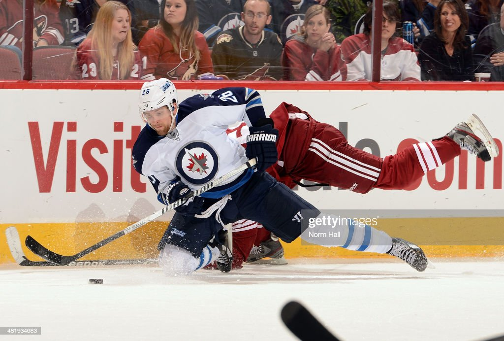 <a gi-track='captionPersonalityLinkClicked' href=/galleries/search?phrase=Blake+Wheeler&family=editorial&specificpeople=716703 ng-click='$event.stopPropagation()'>Blake Wheeler</a> #26 of the Winnipeg Jets plays the puck while falling to the ice against the Phoenix Coyotes at Jobing.com Arena on April 1, 2014 in Glendale, Arizona.