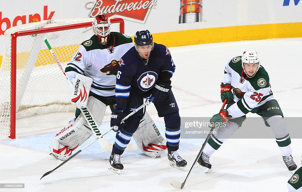 <a gi-track='captionPersonalityLinkClicked' href=/galleries/search?phrase=Blake+Wheeler&family=editorial&specificpeople=716703 ng-click='$event.stopPropagation()'>Blake Wheeler</a> #26 of the Winnipeg Jets positions himself between goaltender Niklas Backstrom #32 and <a gi-track='captionPersonalityLinkClicked' href=/galleries/search?phrase=Jonas+Brodin&family=editorial&specificpeople=7832272 ng-click='$event.stopPropagation()'>Jonas Brodin</a> #25 of the Minnesota Wild as they keep an eye on the play during third period action at the MTS Centre on December 27, 2013 in Winnipeg, Manitoba, Canada.