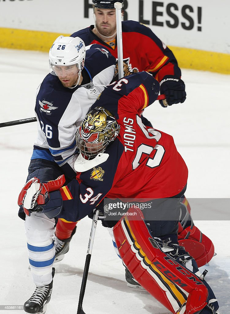 <a gi-track='captionPersonalityLinkClicked' href=/galleries/search?phrase=Blake+Wheeler&family=editorial&specificpeople=716703 ng-click='$event.stopPropagation()'>Blake Wheeler</a> #26 of the Winnipeg Jets runs into goaltender Tim Thomas #34 of the Florida Panthers in front of the net at the BB&T Center on December 5, 2013 in Sunrise, Florida. The Panthers defeated the Jets 5-2.
