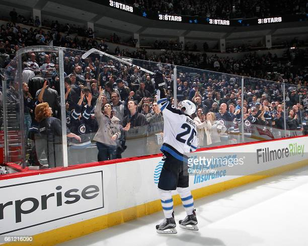 Blake Wheeler of the Winnipeg Jets sends a souvenir stick over the glass to fans after receiving third star honors following a 43 overtime victory...
