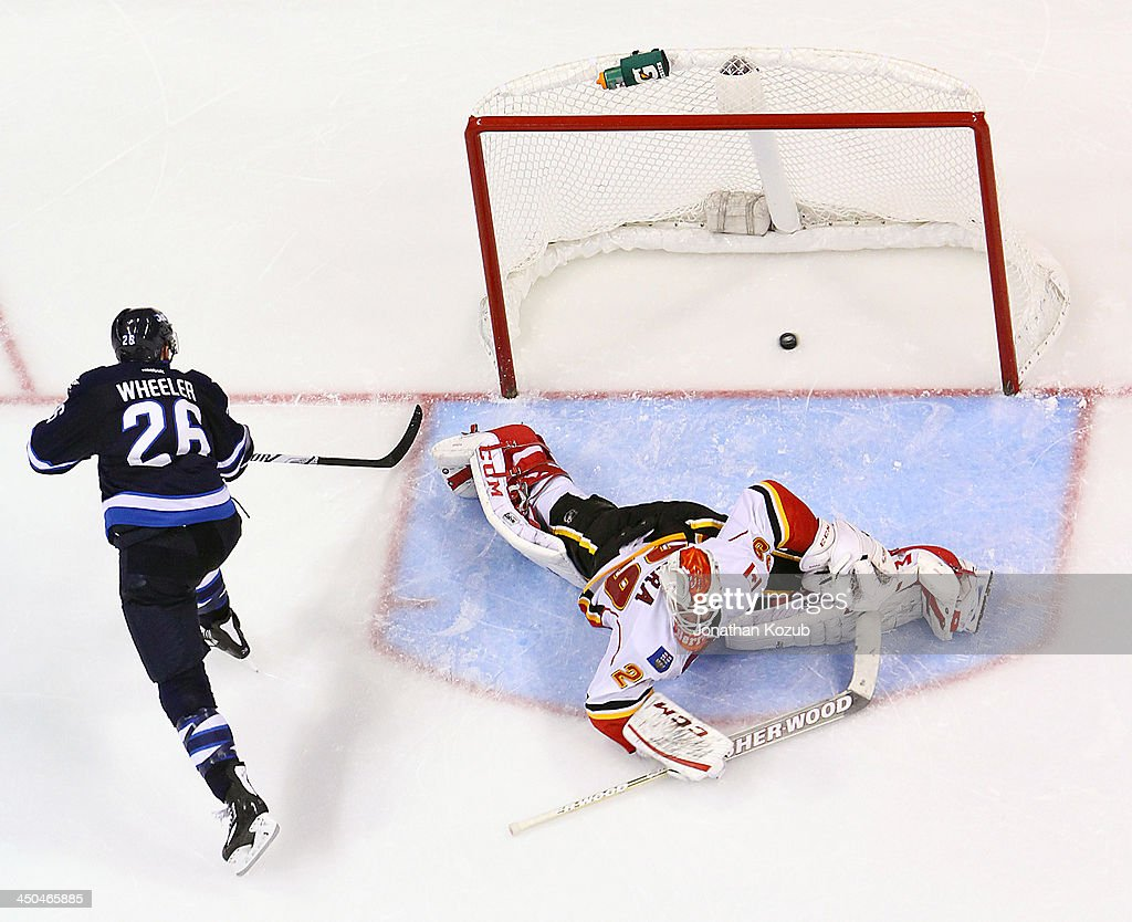 <a gi-track='captionPersonalityLinkClicked' href=/galleries/search?phrase=Blake+Wheeler&family=editorial&specificpeople=716703 ng-click='$event.stopPropagation()'>Blake Wheeler</a> #26 of the Winnipeg Jets shoots the puck over a sprawling Reto Berra #29 of the Calgary Flames during the shootout at the MTS Centre on November 18, 2013 in Winnipeg, Manitoba, Canada.