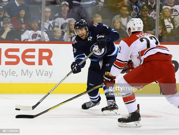 Blake Wheeler of the Winnipeg Jets shoots the puck past a defending Brett Pesce of the Carolina Hurricanes during first period action at the Bell MTS...
