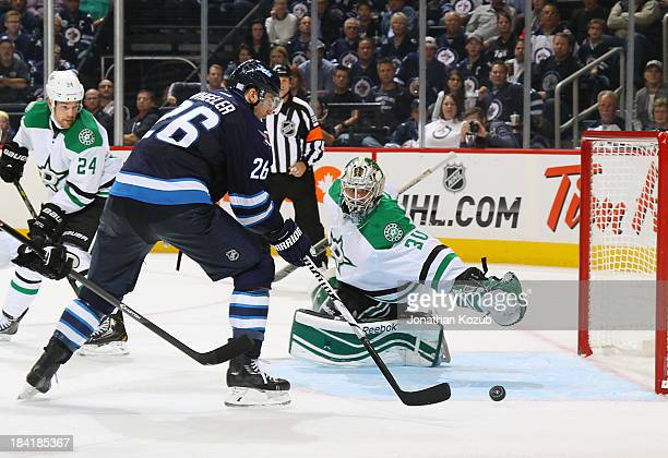 Blake Wheeler of the Winnipeg Jets shoots the puck towards the open net for a third period goal as goaltender Dan Ellis of the Dallas Stars dives...