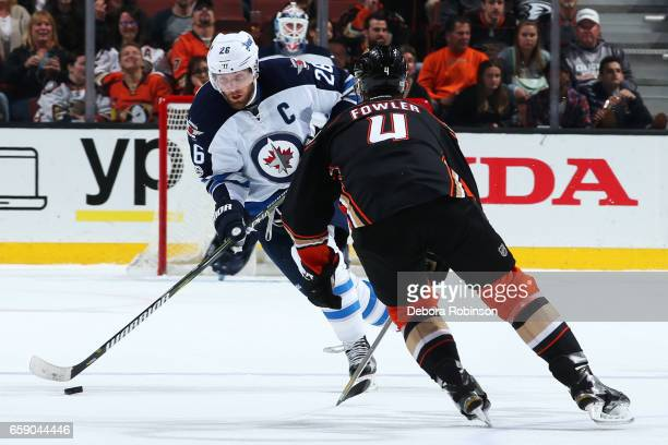 Blake Wheeler of the Winnipeg Jets skates with the puck against Cam Fowler of the Anaheim Ducks during the game on March 24 2017 at Honda Center in...