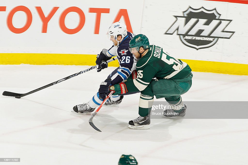 <a gi-track='captionPersonalityLinkClicked' href=/galleries/search?phrase=Blake+Wheeler&family=editorial&specificpeople=716703 ng-click='$event.stopPropagation()'>Blake Wheeler</a> #26 of the Winnipeg Jets skates with the puck with <a gi-track='captionPersonalityLinkClicked' href=/galleries/search?phrase=Nick+Schultz&family=editorial&specificpeople=203252 ng-click='$event.stopPropagation()'>Nick Schultz</a> #55 of the Minnesota Wild defending during the game at the Xcel Energy Center on February 16, 2012 in St. Paul, Minnesota.