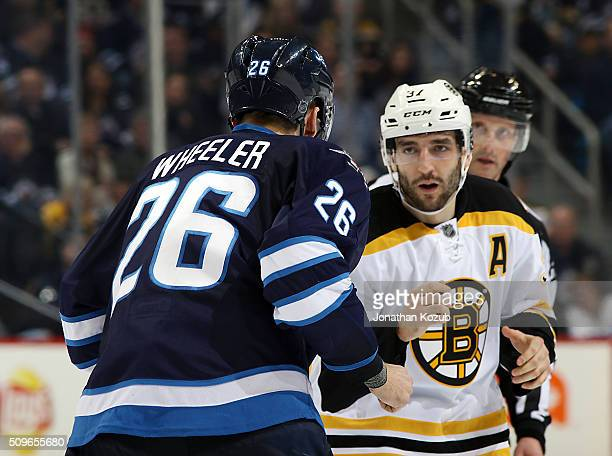 Blake Wheeler of the Winnipeg Jets squares up against Patrice Bergeron of the Boston Bruins during a second period fight at the MTS Centre on...