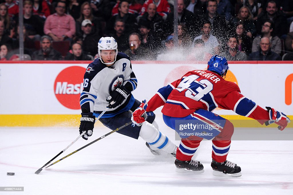 Blake Wheeler of the Winnipeg Jets stops with the puck in front of Mike Weaver of the Montreal Canadiens during the NHL game at the Bell Centre on...