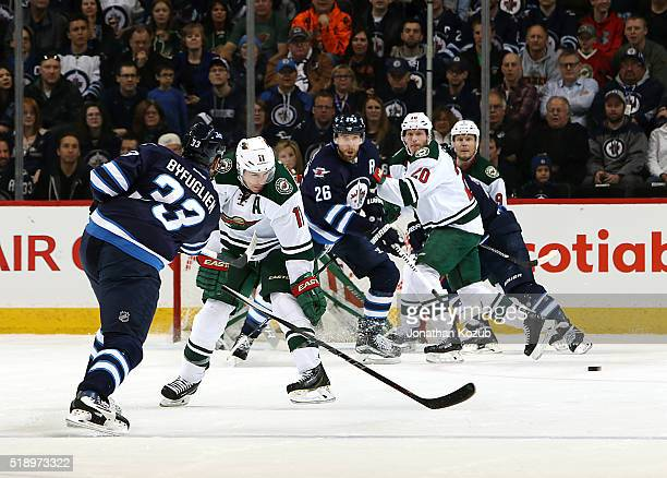 Blake Wheeler of the Winnipeg Jets watches as a point shot by teammate Dustin Byfuglien is deflected wide of the net during first period action...