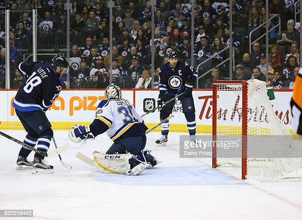 Blake Wheeler of the Winnipeg Jets watches as teammate Bryan Little deflects the puck past goaltender Pheonix Copley of th St Louis Blues for a first...