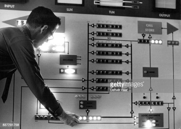 E L Blakley technical training supervisor of the new Western Electric train­ing facility checks a 'word organized store program simulator' a key...