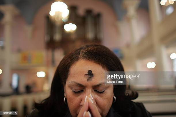 Blanca Gonzalez prays with her forehead marked with ash during Ash Wednesday celebrations at St Paul's Chapel February 21 2007 in New York City The...