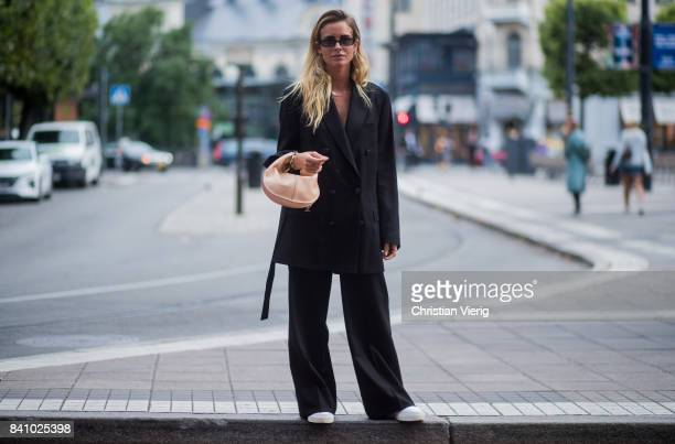 Blanca Miro Scrimieri wearing black coat and wide leg pants outside Rodebjer on August 30 2017 in Stockholm Sweden