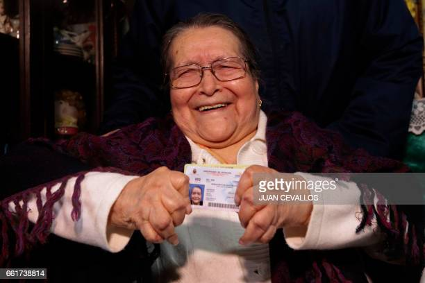 Blanca Rosas shows her voting certificate after casting his vote for Ecuador's presidential runoff at her house in the framework of the 'Vote at...