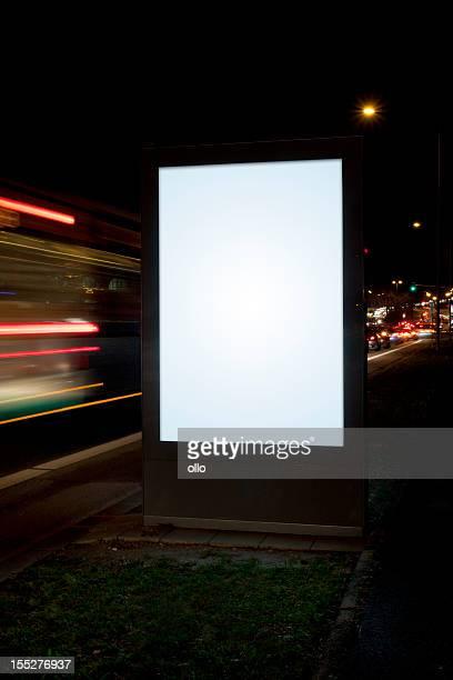 Blank advertising billboard on city street at night