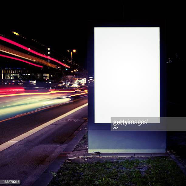 Cartellone pubblicitario vuoto sulla strada di città di notte