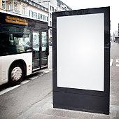 Blank advertising billboard on city street, bus passes