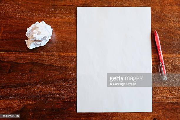 Blank and crumpled sheets of paper on a table