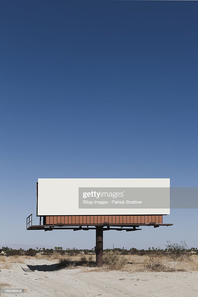 A blank billboard in a desert : Stock Photo