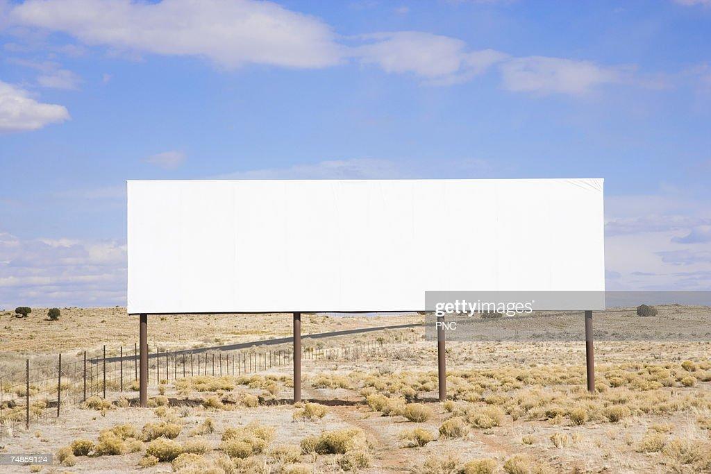 Blank billboard in desert : Stock Photo