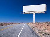 Blank billboard on remote desert road