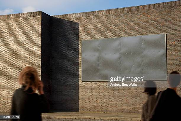 blank billboard with passing pedestrians