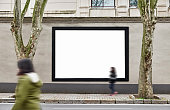 Blank billboards on wall. Wall is made of concrete and gray coloured. There are three billboards standing side by side and oriented vertically. Edges of billboards are black. Billboards are empty so y