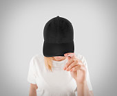 Blank black baseball cap mockup template, wear on women head, isolated, clipping path. Woman in gray hat and t shirt uniform mock up holding visor of caps. Cotton basebal cap design on delivery guy.