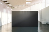 Blank black wall mockup in sunny modern empty gallery, 3d rendering. Dark big stand mock up in museum with contemporary art exhibitions. Large hall interior with wide grey banner exposition template.