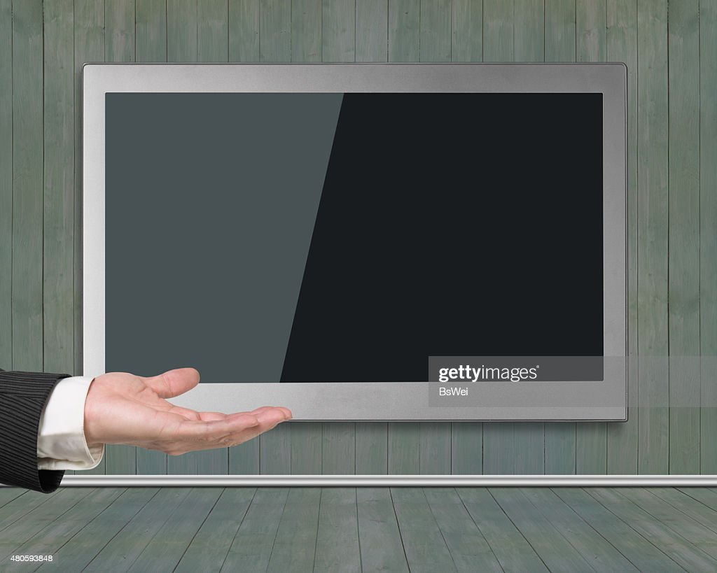 Blank black wide flat TV screen hanging on wooden wall : Stock Photo