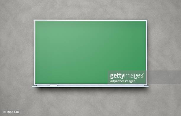 Blank blackboard with chalk on a concrete wall