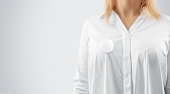 Blank button badge mockup pinned on the womans chest, close up view. Girl wear white shirt and campaign pin mock up. Volunteer round emblem design element. Pesron stand front view with voting symbol