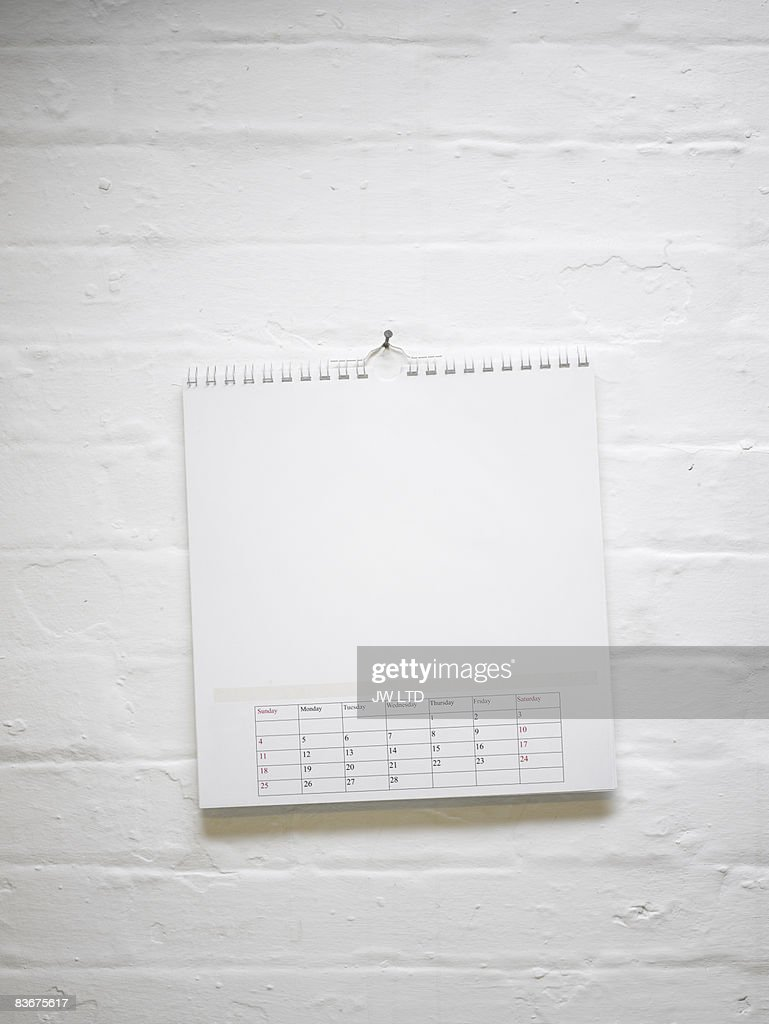 Blank calendar hanging on white brick wall : Stock Photo
