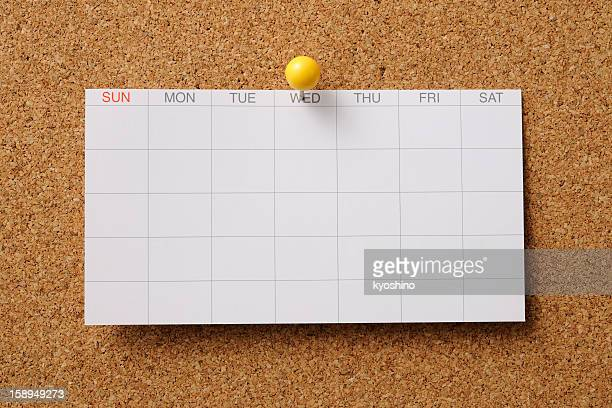 Blank calendar pinned on cork board with yellow thumbtack