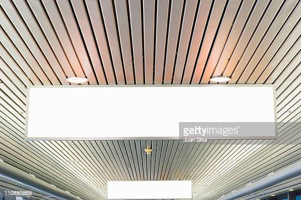 Blank ceiling signs at airport.