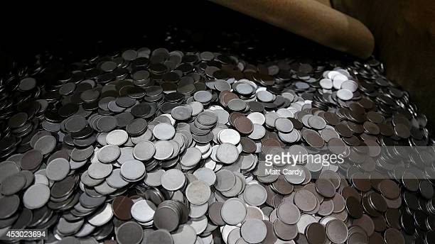 Blank coins that have been produced at the Royal Mint are gathered before being sent to be stamped in the coin press on August 1 2014 in Llantrisant...