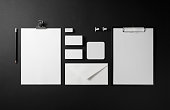 Photo of blank corporate identity. Stationery set on black paper background. Branding mockup. Top view.
