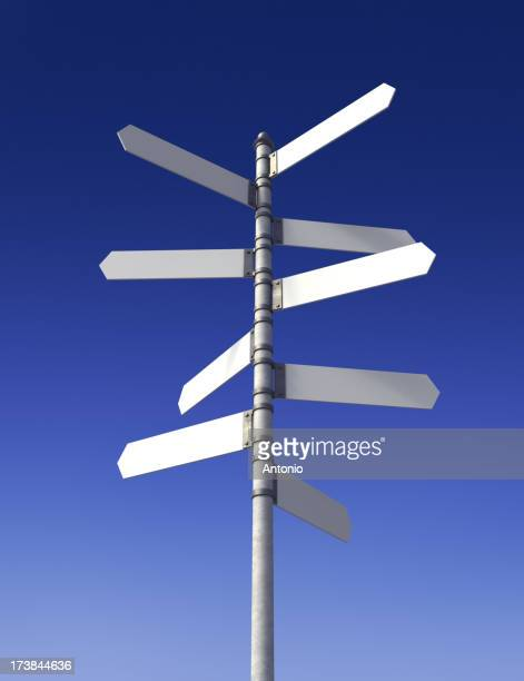 Blank directional street signs against a blue sky