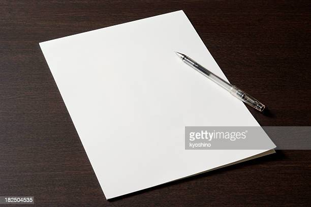 Blank document with pen on wooden desk