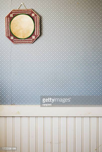 Blank embroidered frame on wallpapered wall