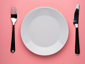 Blank flat plate, knife, fork on a color pink table, top view.