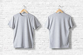 Blank Grey T-Shirts Mock-up hanging on white wall, front and rear side view . Ready to replace your design