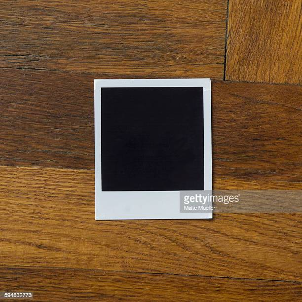 Blank instant camera print on wooden table