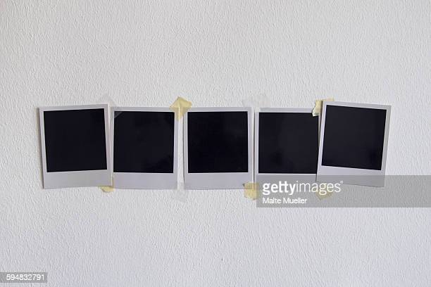 Blank instant camera prints stuck on white wall