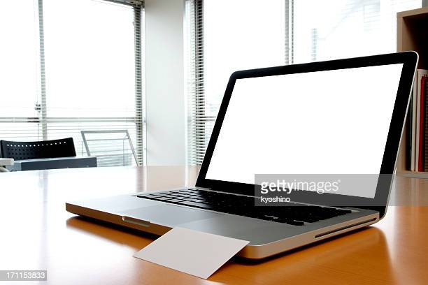Blank laptop with blank business card inside of an office