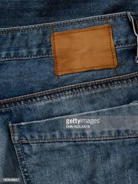 Vaqueros de la etiqueta de cuero blanco sewed en blue jeans.