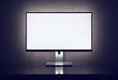 Blank monitor with backlight over gray wall in dark room