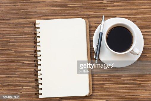 Em branco notebook uma caneta e uma chávena de café : Foto de stock