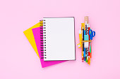 Blank notebook on a stack of colorful notebooks with school supplies. Flat lay. Copy space