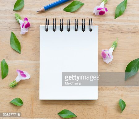 Blank notebook on wood background with flowers : Stock Photo